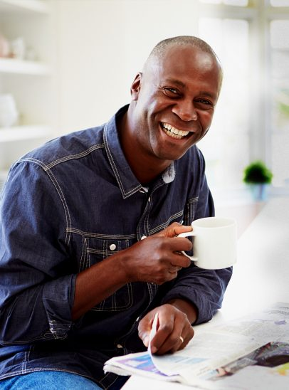 Man smiles drinking coffee after technology has helped sleep