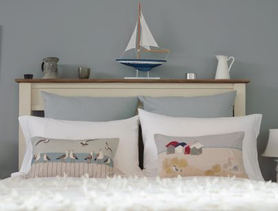 A image of a bed from the kindred origin bedroom range featuring coastal themed cushions and accessories on the headboard.
