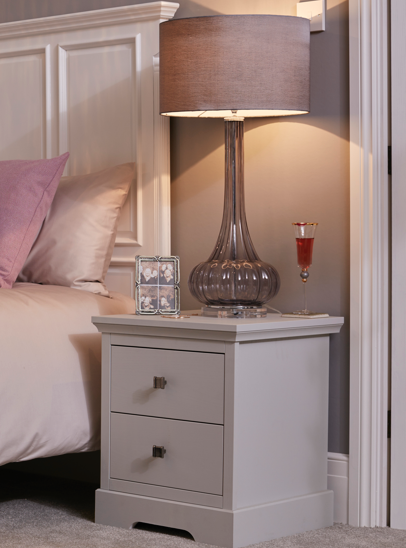 A photograph of our Chapter style 2 bedside table which features a tall glass lamp with a violet shade and a glass of red wine on the table.