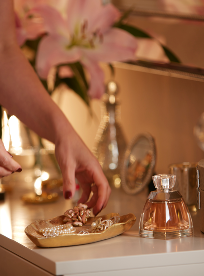 This photograph shows a female hand picking up jewellery out of a golden tray on a dressing table.