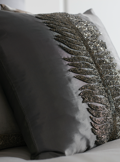 A close up image of the beaded embroidery on a cushion in the Flow Style 1 room set.