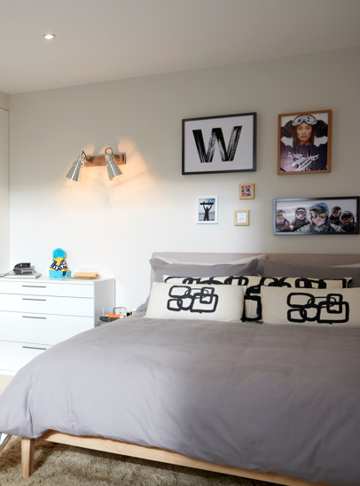 A photograph of the wooden bed frame in the Parity style 2 room set with grey bedding and graphic black and white pillows.