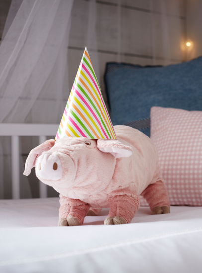 A photograph of the Kindred Chapter style 3 room set featuring a soft toy pig on the bed wearing a stripe party hat.