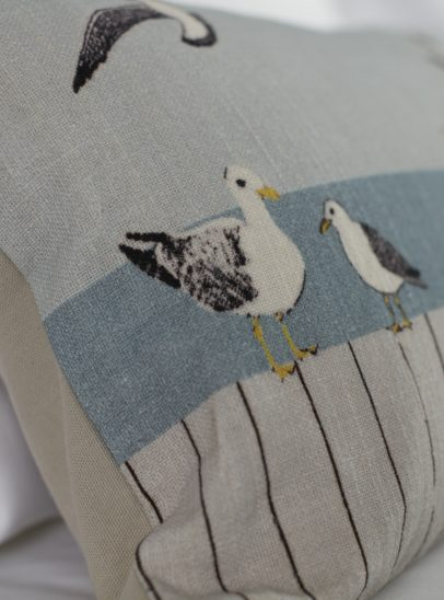 A close up photograph of a coastal themed cushion on a bed featuring neutral colours and seagulls.