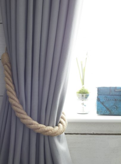 A close up photograph of a pair of grey curtains in with a rope tie.